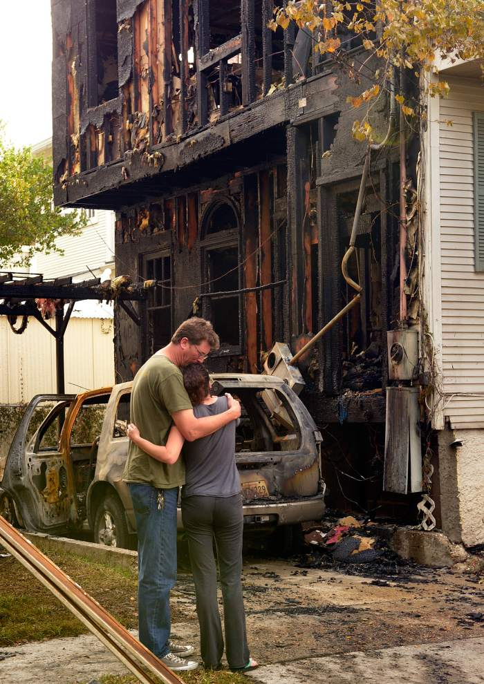 Advocate staff photo by JOHN McCUSKER -- Mark Brown and Erica Centurion embrace in front of the burned out apartment they lived in on Prytania Street. The house and three cars burned on Prytania Street at Constantinople in the early morning hours Thursday, November 6, 2014 after an apparent fire bombing.